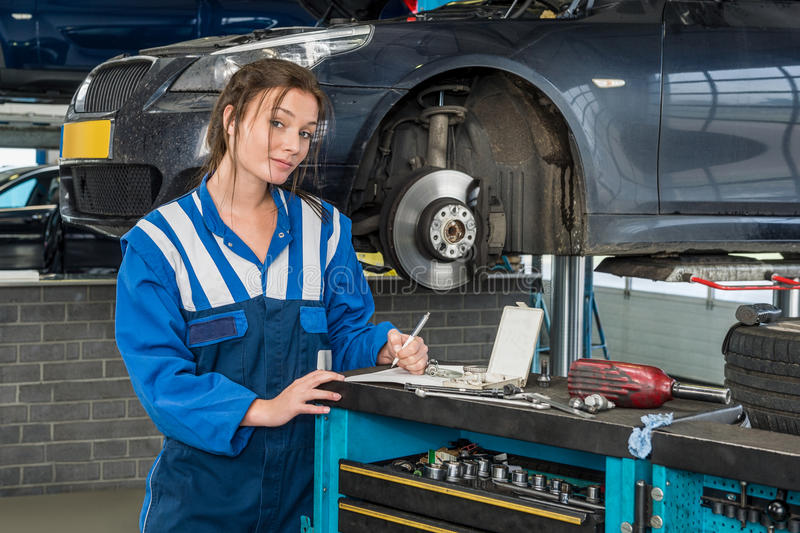Confident Female Mechanic Writing Notes In Garage stock photos