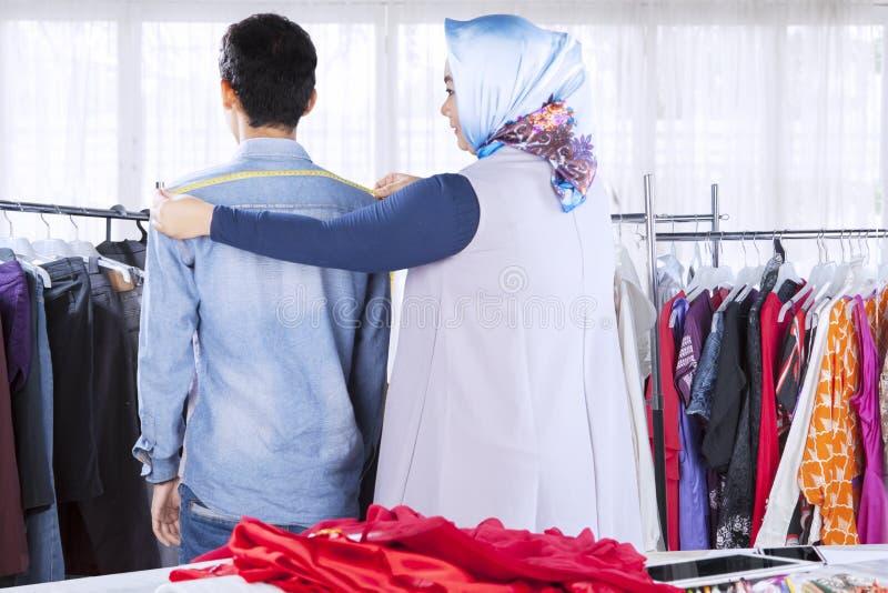 Confident female muslim fashion designer measuring clients shoulder stock photos