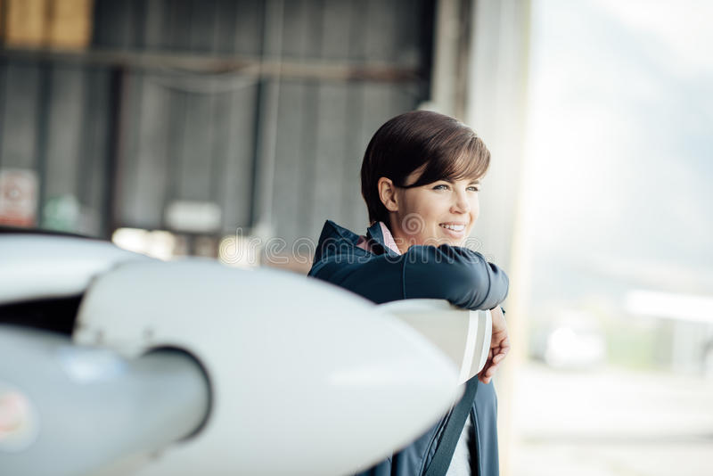 Confident female pilot in the hangar. Confident young female pilot posing next to a light aircraft and smiling, she is leaning on the propeller and looking away stock images