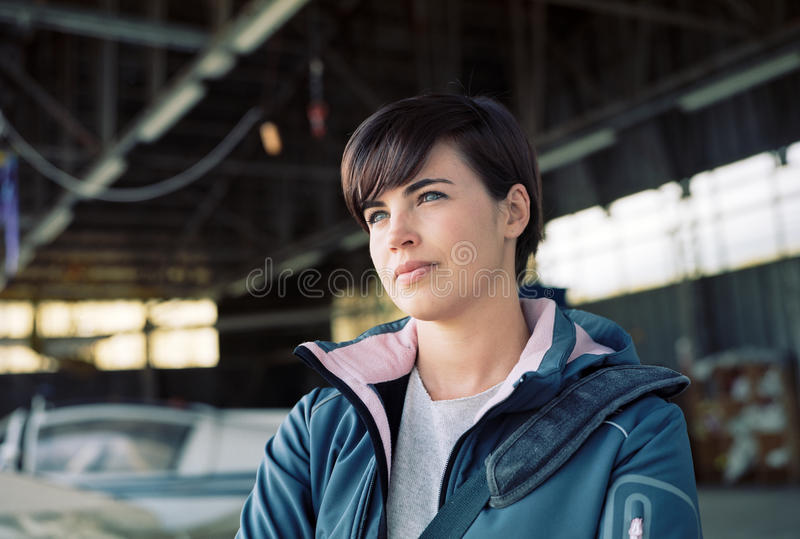 Confident female pilot posing in the hangar. Confident young female pilot posing in the hangar, airplane on the background stock images