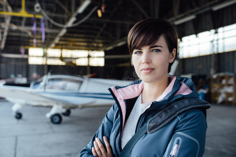 Confident female pilot posing in the hangar. Confident young female pilot posing in the hangar with arms crossed, airplane on the background royalty free stock photos