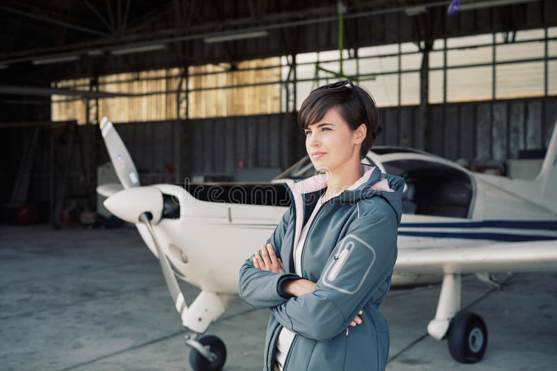 Confident female pilot posing in the hangar. Confident young female pilot posing in the hangar with arms crossed, airplane on the background stock photos
