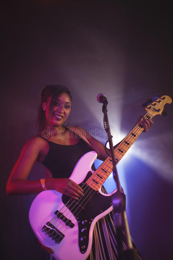Confident female singer holding guitar on stage in nightclub royalty free stock image