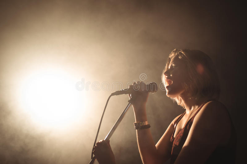 Confident female singer performing in illuminated nightclub. Low angle view of confident female singer performing in illuminated nightclub stock image