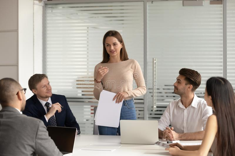 Confident female speaker standing, explaining project results to multiracial colleagues. stock images