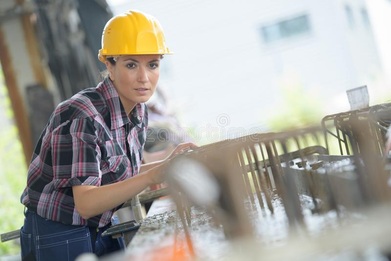 Confident female worker holding pipes at construction site royalty free stock images