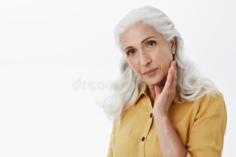 Confident and feminine elegant elderly woman with long white hair in stylish yellow trench coat touching face gently and royalty free stock image
