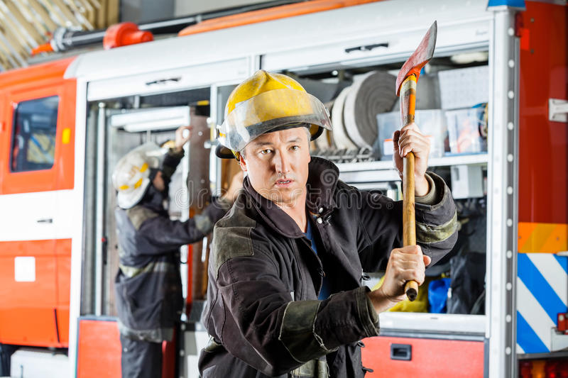 Confident Fireman Holding Axe At Fire Station royalty free stock photos