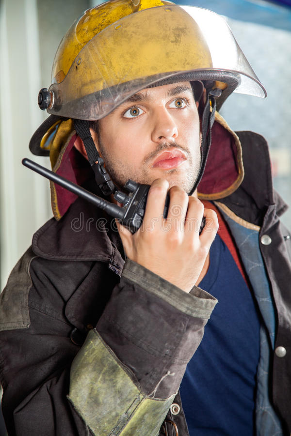 Confident Fireman Using Walkie Talkie. Confident male fireman looking away while using walkie talkie at fire station stock photos