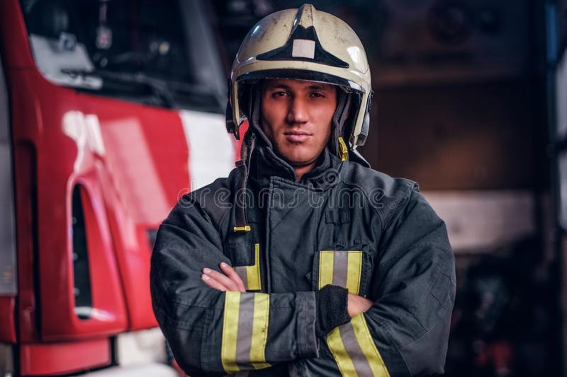 A confident fireman wearing protective uniform standing next to a fire engine in a garage of a fire department, crossed. Confident fireman wearing protective royalty free stock images