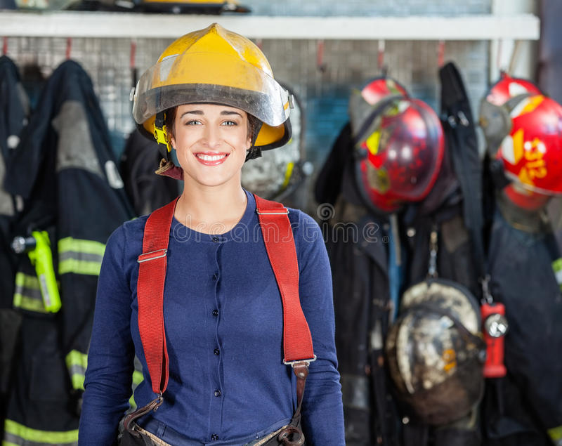 Confident Firewoman Standing At Fire Station. Portrait of confident young firewoman standing at fire station stock image