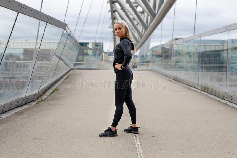 Fit Female Beauty in Black Workout Wear Standing At Modern Bridge In City royalty free stock photo