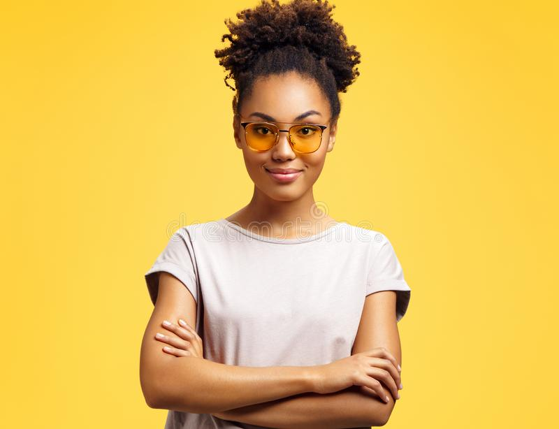 Confident girl holds hands crossed, wears sunglasses. stock photography