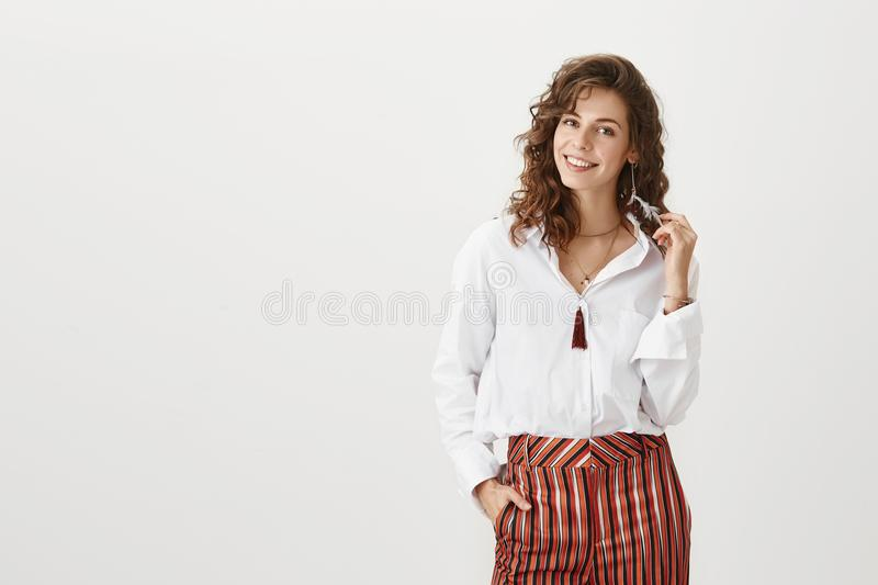 Confident girl on party with her girlfriends. Good-looking caucasian female in trendy blouse and striped trousers stock images