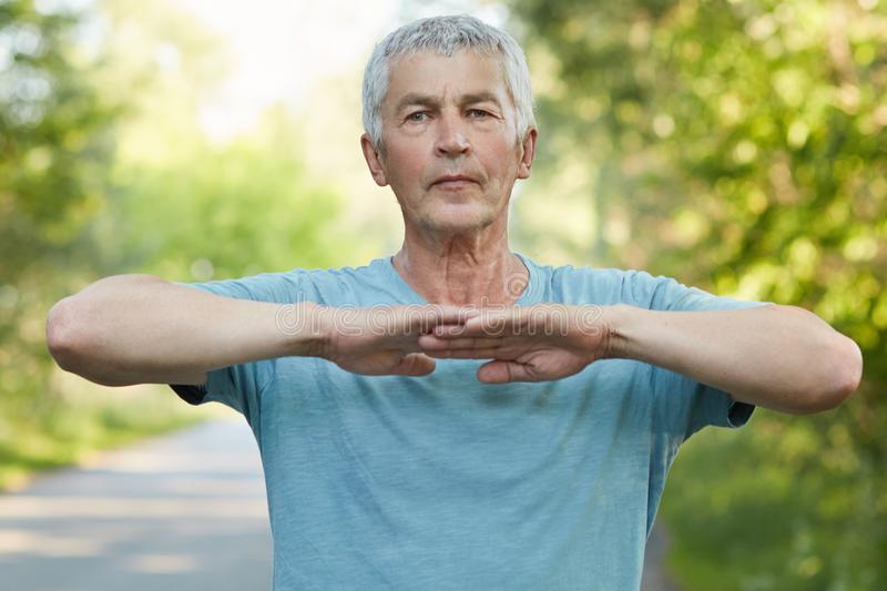 Confident grey haired male stretches hands, does physical exercise or workout in open air, has self assured facial expression stan stock photo