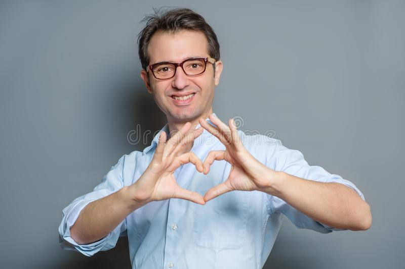 Man making out of the hands heart on gray stock images