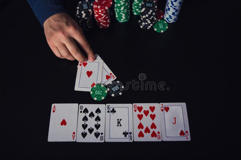 Confident guy poker player taking a large stack of chips to his bank, winning at the casino gaming table having royal flush cards royalty free stock photo