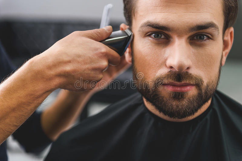 Confident guy sitting at beauty salon. Calm young men is getting haircut by electric machine at hairdressers royalty free stock photography