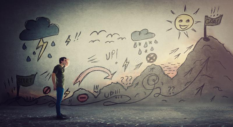 Confident guy starting a life quest with obstacles drawn on wall. Self overcome imaginary mountain, climbing ups and downs for royalty free stock image