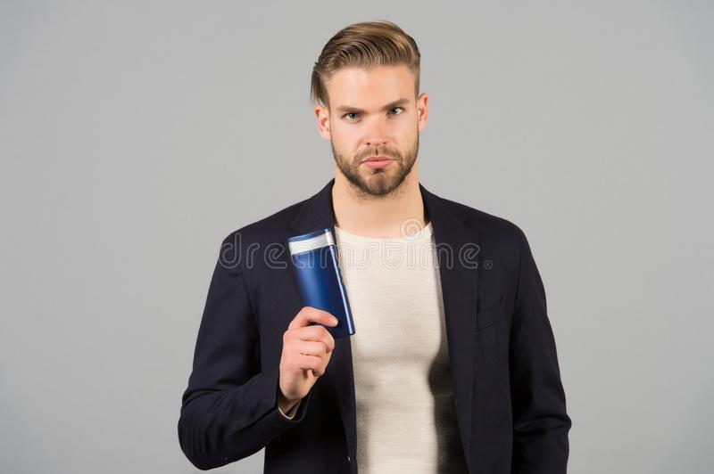 Confident in hair care product. Man stylish hairstyle holds bottle hygienic product grey background. Switch matte. Products if thinning. Men hair thins out royalty free stock photography