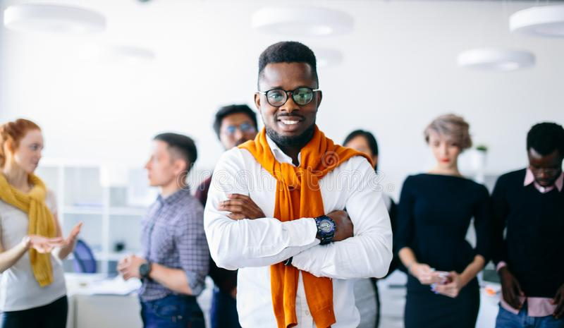 Confident handsome black boss with crossed arms in front of co-workers royalty free stock photo