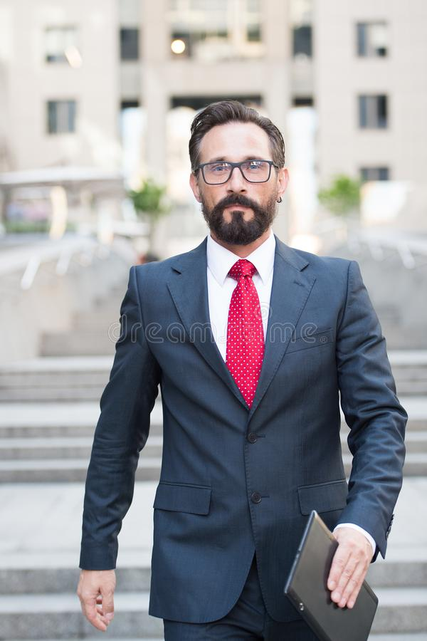 Confident handsome businessman walking down city stairs. Waist up of handsome bearded businessman keeping a tablet in hand while walking down the city stairs and stock photography
