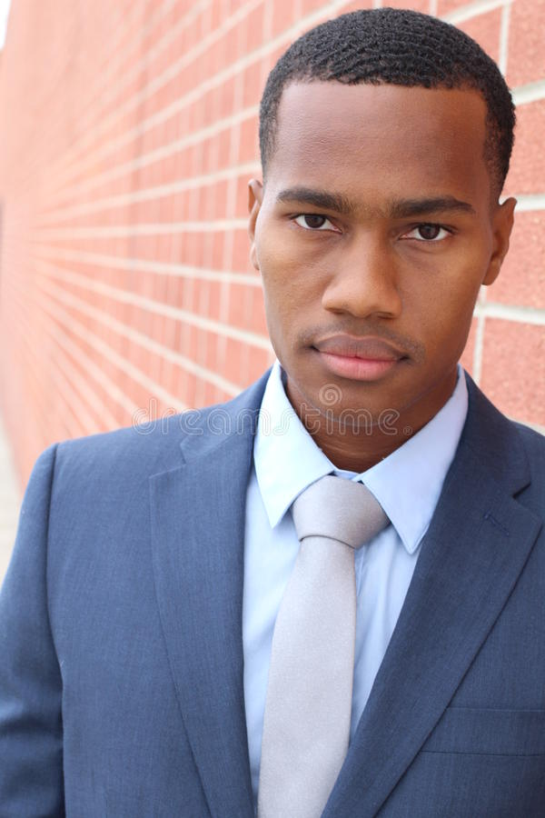 Confident and handsome. Confident young African man in formalwear looking at camera while standing against gorgeous red brick wall royalty free stock image