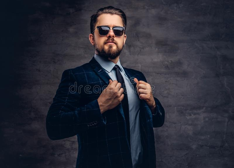 Confident handsome fashionable middle-aged man with beard and hairstyle dressed in an elegant formal suit and sunglasses stock images