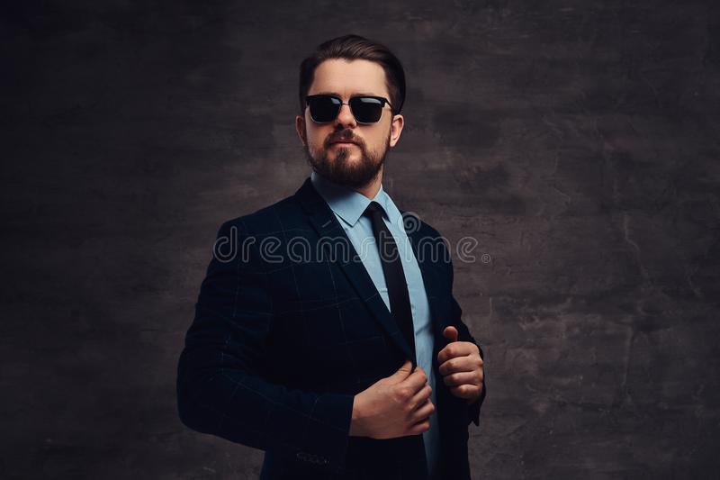 Confident handsome fashionable middle-aged man with beard and hairstyle dressed in an elegant formal suit and sunglasses royalty free stock photos