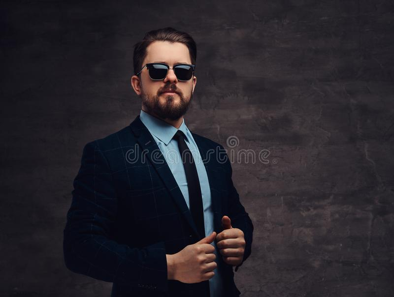 Confident handsome fashionable middle-aged man with beard and hairstyle dressed in an elegant formal suit and sunglasses royalty free stock images