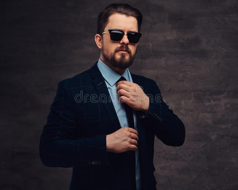 Confident handsome fashionable middle-aged man with beard and hairstyle dressed in an elegant formal suit and sunglasses royalty free stock photography