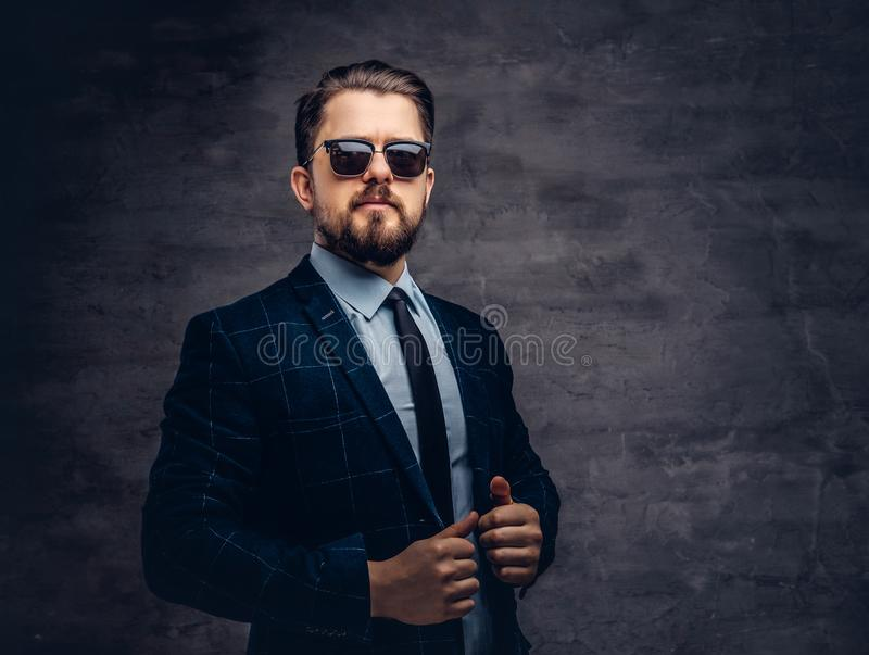 Confident handsome fashionable middle-aged man with beard and hairstyle dressed in an elegant formal suit and sunglasses royalty free stock photo