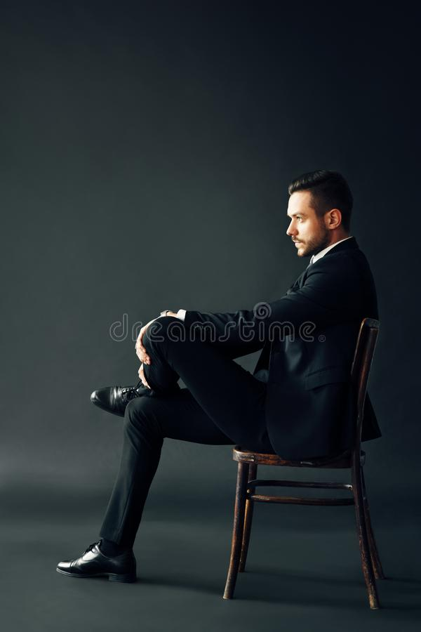 Confident handsome man in black suit sitting on the chair on dark backround royalty free stock photo