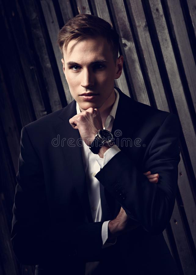 Confident handsome man with strained look posing in blue fashion. Suit and white style shirt and fashion watch on the hand on black wall wooden background royalty free stock photos