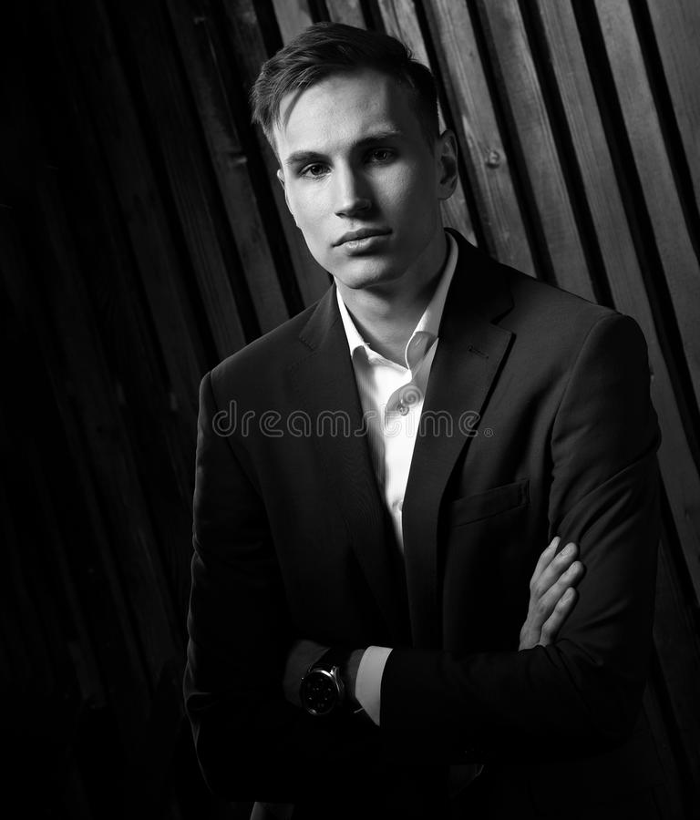Confident handsome man with strained look posing in blue fashion. Suit and white style shirt and fashion watch on the hand. Closeup portrait. Black and white stock image