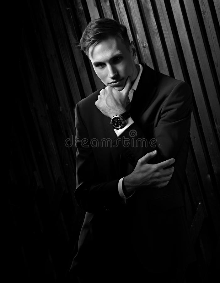 Confident handsome man with strained look posing in blue fashion. Suit and white style shirt and fashion watch on the hand on black wall wooden background royalty free stock photography