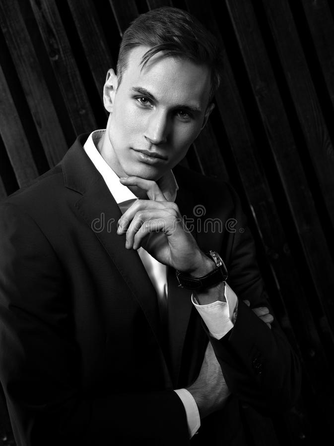 Confident handsome man with strained look posing in blue fashion. Suit and white style shirt and fashion watch on the hand on black wall wooden background royalty free stock images