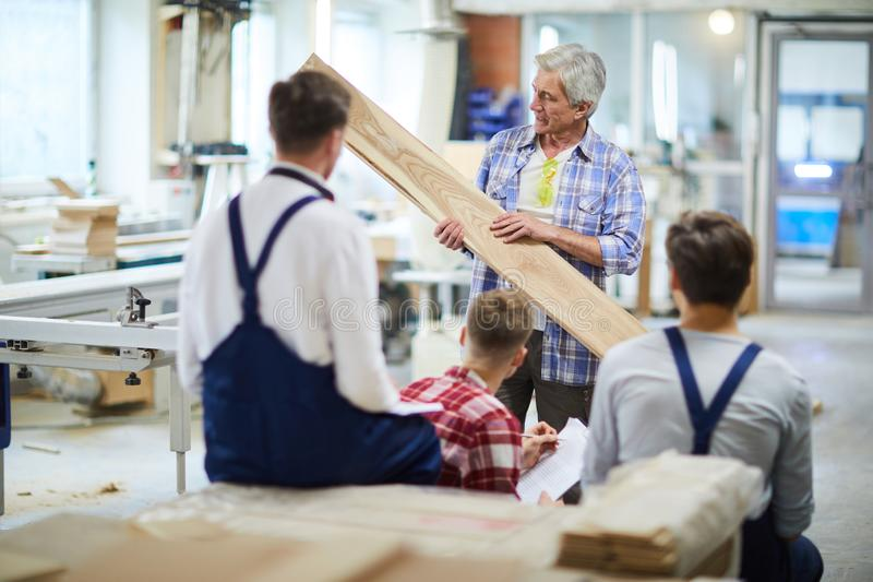 Confident carpenter teaching students to process wood royalty free stock image