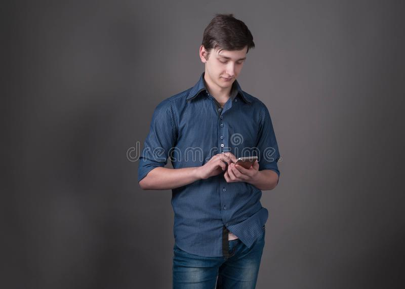 Confident handsome young man in blue shirt holding and using smartphone on grey background. With copy space royalty free stock image