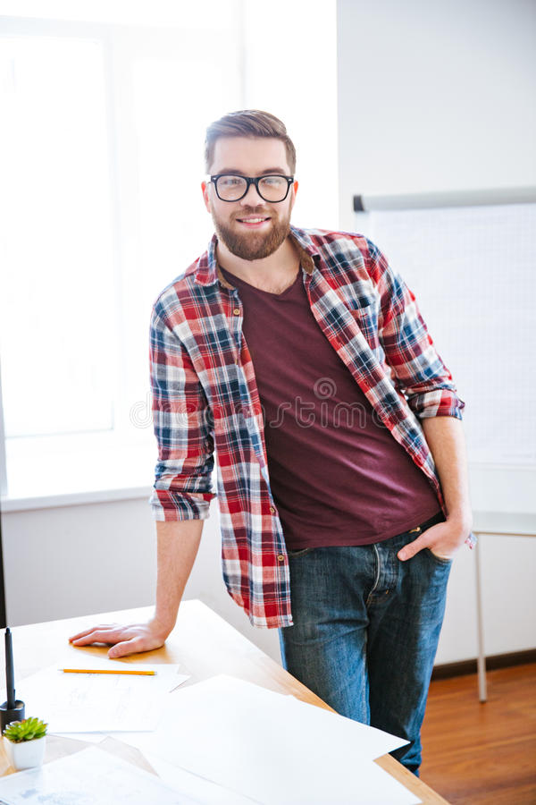 Confident happy bearded man standing in conferece room near flipchart royalty free stock image