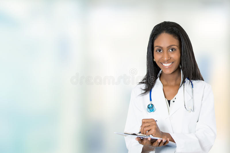 Confident happy female doctor medical professional writing notes royalty free stock photo
