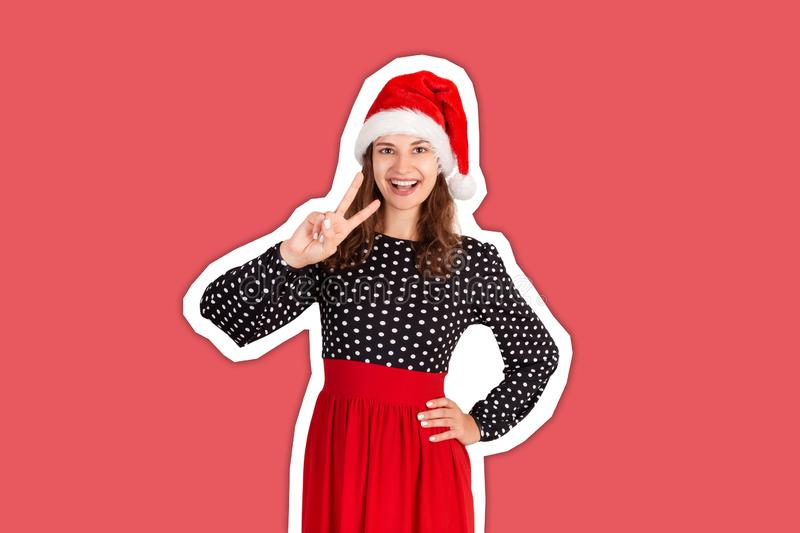 Confident happy and outgoing woman in dress, showing victory or peace gesture and winking with broad smile at camera. Magazine royalty free stock photo