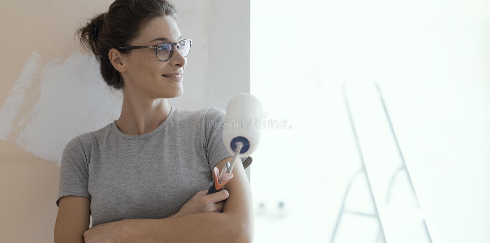 Confident happy woman painting walls at home stock images
