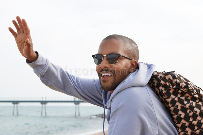 Confident happy young African-American man hipster in sport hoody and sunglasses looking a friend on the beach. stock photography