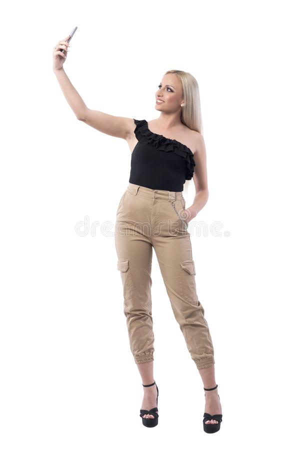 Confident happy young stylish fashionable woman taking selfie and smiling at camera royalty free stock photo