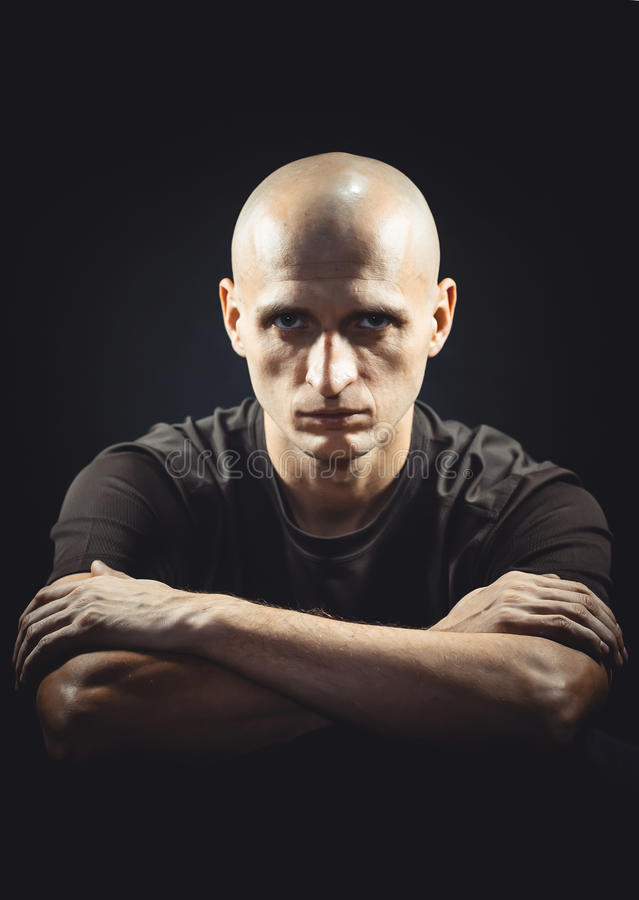 Confident, harsh and strong. Portrait of a bald shaven man on a black background royalty free stock photos