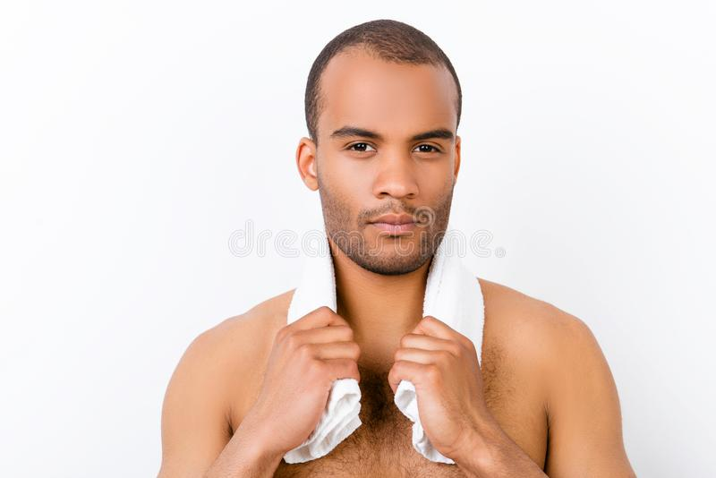 Confident harsh young mulatto nude man is standing on the pure w. Hite background, with towel around his neck. So hot and attractive, fashionable and brutal royalty free stock photos