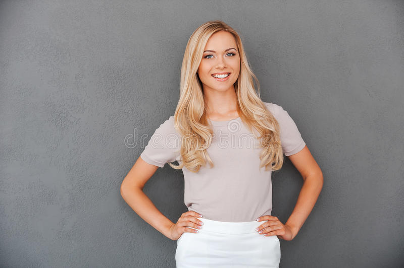 Confident in her abilities. Smiling young blond hair woman holding hands on hips and looking at camera while standing against grey background stock photography