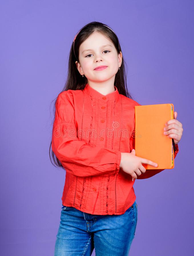 Confident in her knowledge. Adorable small girl holding book with orange cover. Cute little child with book knowledge in. Hands. Knowledge and skills. Knowledge stock photo