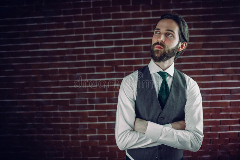 Confident hipster with arms crossed looking away. Against brick wall royalty free stock photos